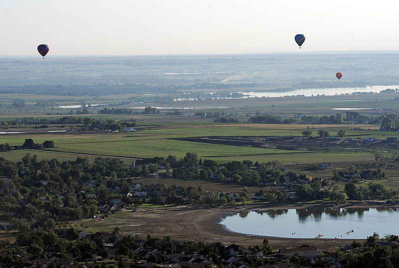 Hot air balloons fly over Boyd Lake in Loveland Friday.