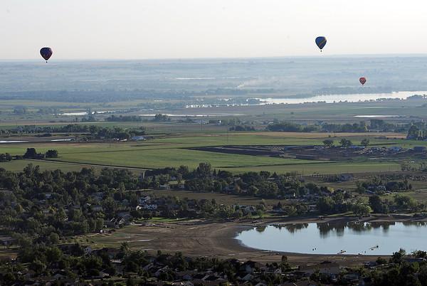 Hot air balloons fly over Boyd Lake in Loveland Friday.