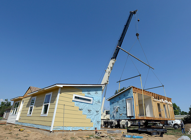 With the help of a crane, crews work to move half of a home on to it's foundation Friday morning in Loveland. The Habitat for Humanity home was built by students in Loveland High School's Geometry in Construction class.