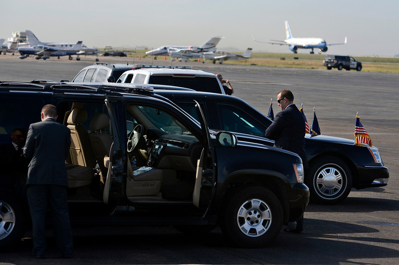 Members of the Sercret Service stand on the tarmac at the Fort Collins-Loveland Municipal Airport as Air Force One, back right, taxis to the runway Wednesday in Loveland.