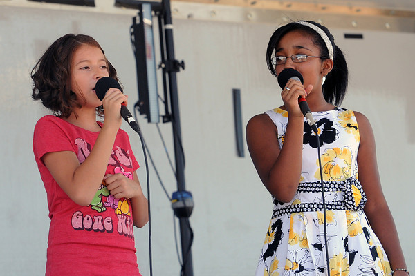 Alexis Hernandez, 11, left, and Breanna Davis, 11, sing a song together during a break in competition for Loveland's Got Talent on Saturday, Aug. 25, 2012 at Fairgrounds Park.