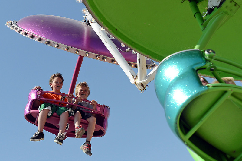 Braden Flores, left, and Trace Kendrick are all smiles as they take a spin on one of the carnival rides during the Larimer County Fair on Saturday, Aug. 4, 2012 at The Ranch.