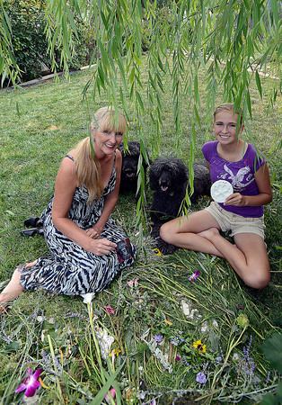 Darlene St. John, left, and her daughter Morgan St. John, 14, pose for a photo near the willow tree and bed of flowers where their beloved standard poodle, Lily, was euthanized recently. Their dogs Caviar, left, and Lulu, right, who also miss Lily dearly, sit with them in the backyard of their Loveland home.