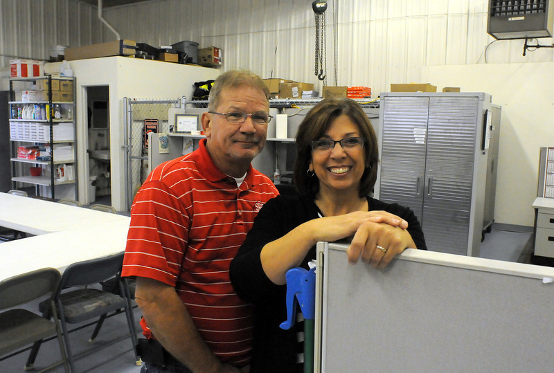 Skip and Diane McIntosh stand at a cubicle in Safe Site's current building east of Loveland. The room, equipped with large garage doors, serves as a storage area, conference room and office space. The McIntoshes recently bought a much larger building near the Loveland airport for their two businesses. (Photo by Craig Young)