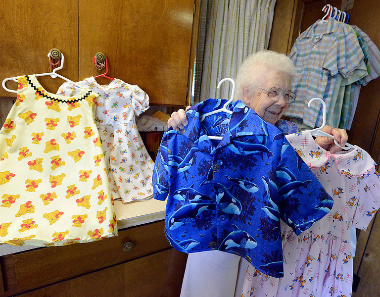 Judy Olson of Campion shows off some of the dresses and shirts she sews to send to orphanages overseas through International Children's Care.