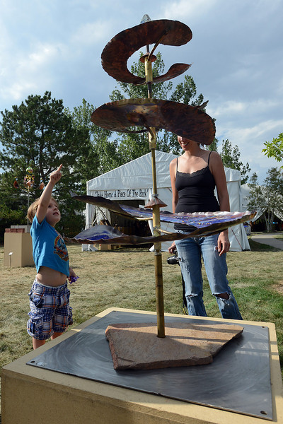 "Two-year-old Ivan Schefter and his mother Ani Rains-Schefter look at a sculpture called ""Triple Dragon III"" by Susan Pascal Beran during Sculpture in the Park on Saturday, Aug. 11, 2012 at the Benson Sculpture Garden."