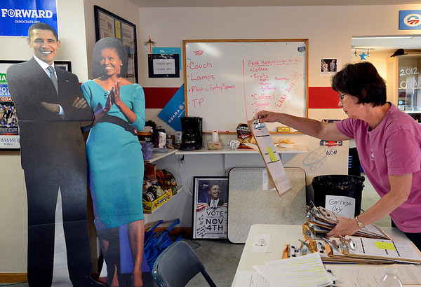 With a cardboard cutout of President Barack Obama and the First Lady Michelle Obama watching, Susan Malmstadt, a volunteer for the Obama for America campaign, prepares packets for people who canvas to register folks to vote, Thursday at the Obama field office in Loveland.