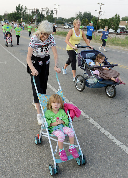 Valley 5000 road race participants and Loveland residents, from left, Ellen Javernick with her granddaughter Meg Bakker, 2 1/2, and Lindsay Daniels with her daughter Carley Lou Daniels, 2 1/2 head out on the course at the start of the race on Friday, Aug. 17, 2012 at Fairgrounds Park.