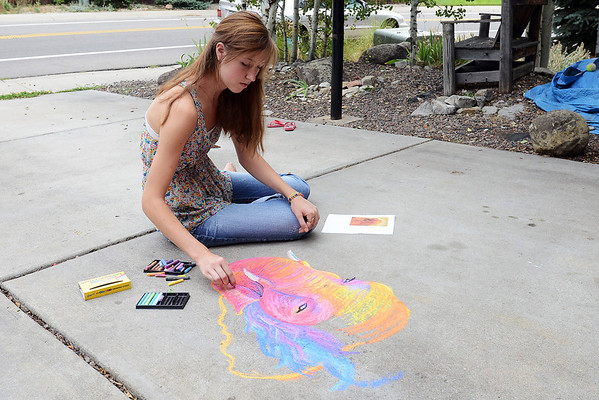 Loveland High School art student Hannah Circenis demonstrates chalk drawing on the driveway of her home on Aug. 22, 2012. Hannah will be participating in Pastels on Fifth event again this year drawing a greyhound dog with chalk.