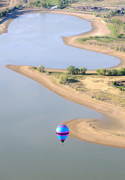 A hot air balloon flies over Boyd Lake in Loveland Friday morning.
