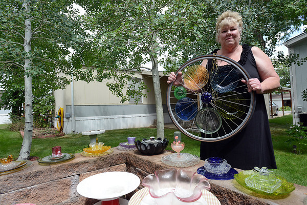 Loveland-based artist Sherry Stockley poses recently with some examples of her creations crafted out of a variety of glassware.