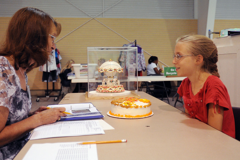 Taylor Lyle, 11, right, chats with cake decorating judge Kathleen Hettinger during the 4-H Interview Judging on Tuesday, July 31, 2012 at the Thomas M. McKee 4-H, Youth & Community Building at The Ranch.