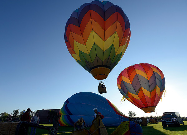 Crew members rig hot air ballons as other balloons launch Friday in Loveland.