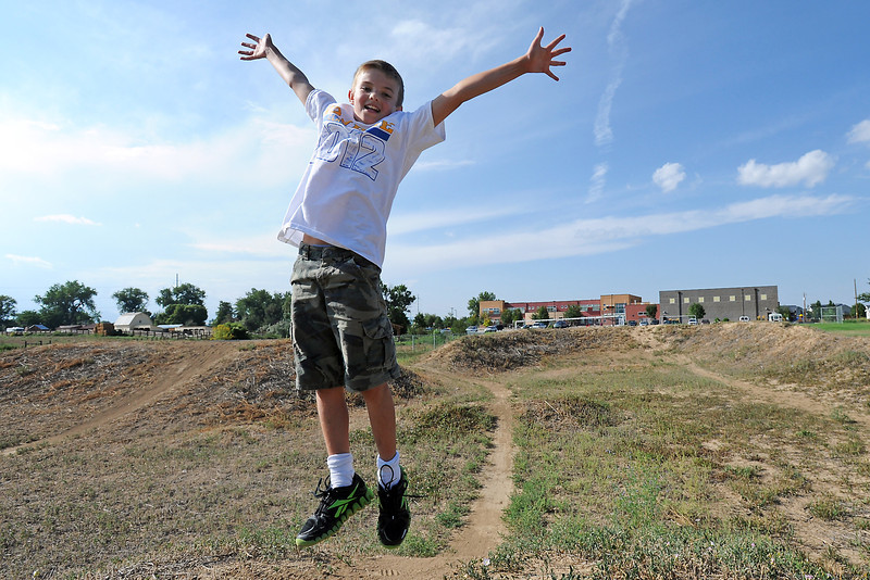 Eleven-year-old Dacota Warner jumps in the air as he poses for a picture on one of the mounds at the BMX track adjacent to the Boys and Girls Club in Loveland on Thursday, Aug. 23, 2012.