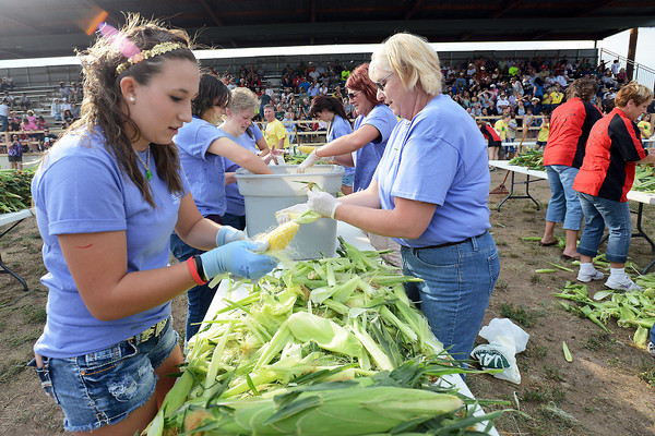 Devan Pacella, 14, left, and Norma Kunz, front right, and other members of Team Aspen House shuck corn during a heat of the corn shucking contest Friday, Aug. 24, 2012 as part of the Old Fashioned Corn Roast Festival at Fairgrounds Park.