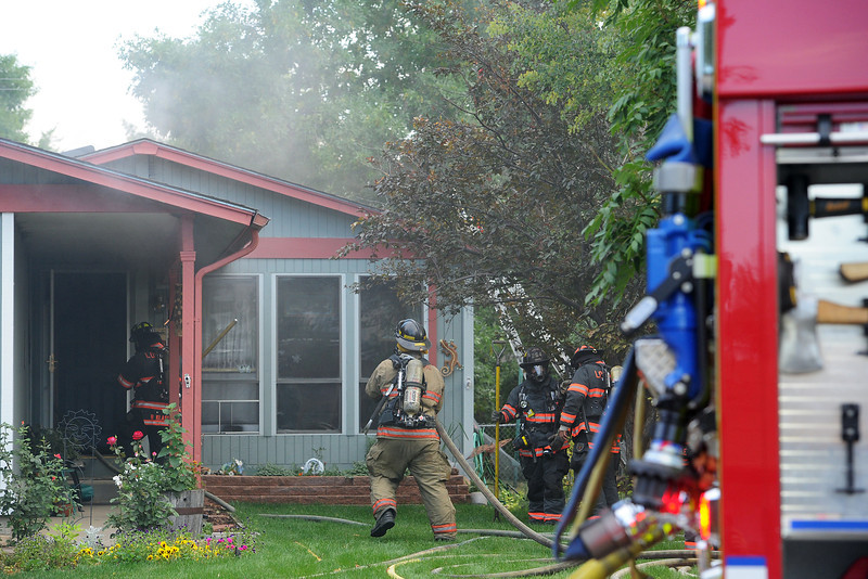 Firefighters work the scene of a house fire on Thursday, Aug. 23, 2012 at 616 W. 9th St. in downtown Loveland.