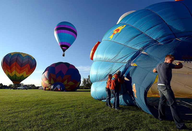 Ethan Young of Loveland, far right, helps a crew inflate a hot air balloon as others launch Friday morning at North Lake Park in Loveland.