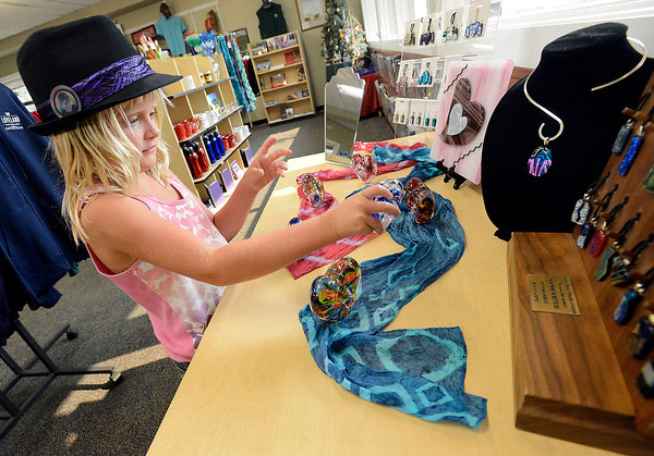 Emalee Larez, 6, looks at a glass heart for sale Tuesday at the Loveland Visitor's Center. She was visiting Loveland with her family from Kimball, Nebraska.