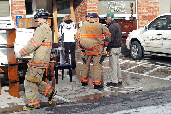 Art Koldeway, right, talks with Lt. Jason Starck of the Loveland Fire and Rescue Dept. as firefighters and others carry boxes full of papers and office furniture outside after Koldeway's building, located at 2530 Abarr Dr. , was flooded when a fire sprinkler system pipe burst.