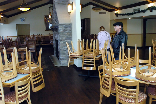 Fort Collins residents Terrie and Chuck Liss walk through the dining area at The Wayside Inn in Berthoud on Friday while examining the property that will be sold at auction on Monday.