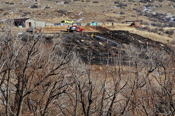 Firefighters spray down hot spots from a grass fire just south of Masonville early Thursday afternoon. Firefighters responded to the blaze just after noon and had it contained less than an hour later.