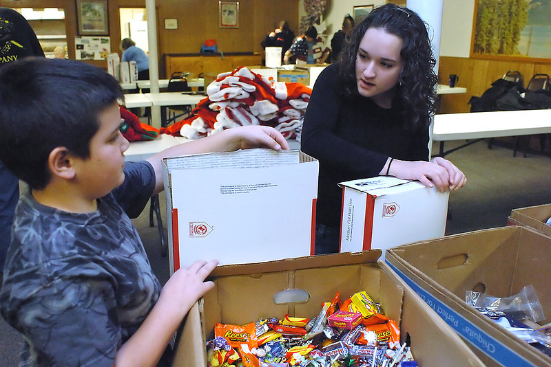 Travis Pflock, 8, left, and Lexi Pflock, 17, pack donated items like toiletries, food, stationary, cards and other items into boxes while volunteering with others Dec. 5 at The Associated Veterans Club to prepare care packages for soldiers stationed in Afghanistan.