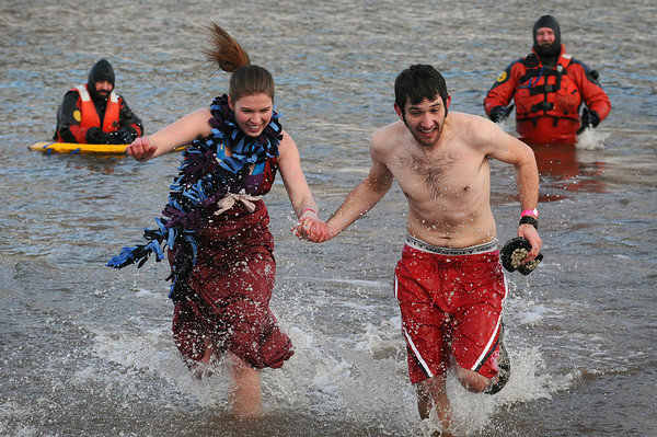 """Colorado State University students Megan Vucasovich, second from left, and Michael Morrow run to the shore after plunging into Horsetooth Reservoir during the """"Freezin' for a Reason"""" polar bear plunge on Thursday in Fort Collins. Larimer County Dive Rescue Team members Wes Grogan, left, and Dave Dennis wait in the background just in case. The plunge, hosted by the CSU Junior Greek Council, raised money for the Family Center/La Familia, a bilingual education center that helps at risk families."""