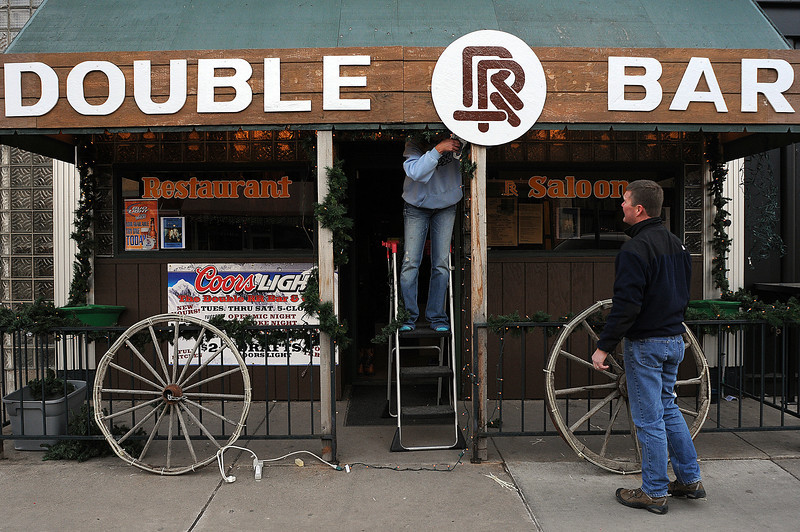 Double RR Bar and Grill owner Kyle Von Eiff, right, and bar manager Linda Harms decorate the front of the establishment on Tuesday in Downtown Loveland.