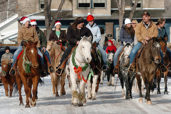 Members of No Tenderfoots Trail Riders ride on horseback along Adams Ave. in downtown Loveland on Saturday while singing Christmas carols.