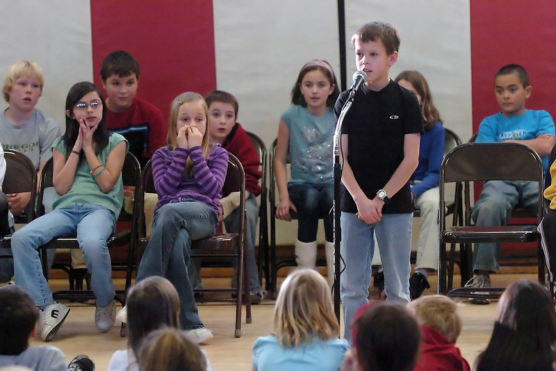 "Nine-year-old Kellis Ward stands at the microphone as he spells a word during a Spelling Bee at Garfield Elementary School on Thursday. Kellis finished in first place after second place finisher Allison Atchley, 9, missed the word ""velocity."" The rest of the top-ten finishers who all qualified for the District Bee in January are Connor Frey, 9, Evyn Batie, 9, Walker Grove, 9, Max Ramos, 10, Faith Sterling, 10, Antoinette Despain, 10, Kyle Whittle, 9, and Kenzee Bollar, 10."
