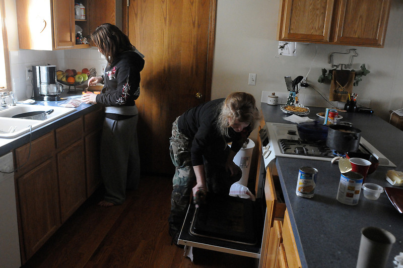 "Starr Blanchard, right, and her daughter Kellie Mansfield, 14, work in the kitchen while preparing a holiday meal on Christmas Eve. Blanchard moved into the home in 2000 with her five children and the help of Habitat for Humanity. ""I can't thank Habitat enough,"" said Blanchard. ""Our home has been a source of stability."""