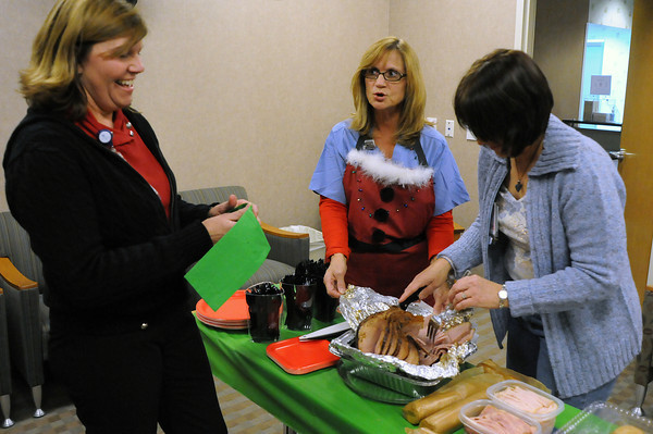Nurses and staff of the Ob/Gyn department, from left, Barb Gindl,Sherry King and Patty Swanson share a laugh as they cut a ham during a potluck on Wednesday at McKee Medical Center. Some hospital workers must celebrate the holidays while at work and many at the McKee do it by sharing food.