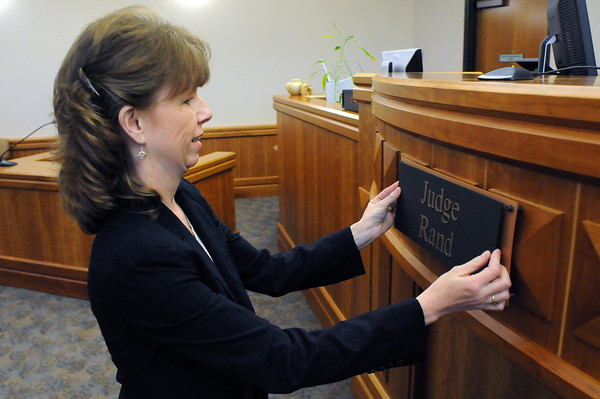Courtroom Clerk Kim Counts places a plaque for the judge she will work for, Judge Robert Rand, following a ceremony to swear him in on Monday at the Larimer County Justice Center in Fort Collins.