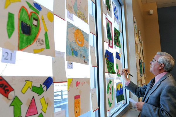 Mayor Cecil Gutierrez judges drawings on Wednesday at the Larimer County Boys and Girls Club in Loveland. Children from all of the Boys and Girls Clubs in Larimer County made drawings for the 4th annual Holiday Card Contest sponsored by McWhinney.