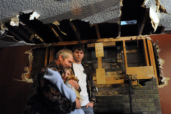 Joe Huggins hugs his 11-year-old daughter Amanda as the two and Amanda's brother Alec, 18, hold a press conference on Sunday at their home in Fort Collins. Amanda alerted three other siblings who were in the house to an early morning fire on Saturday that started in the fireplace in the family room.