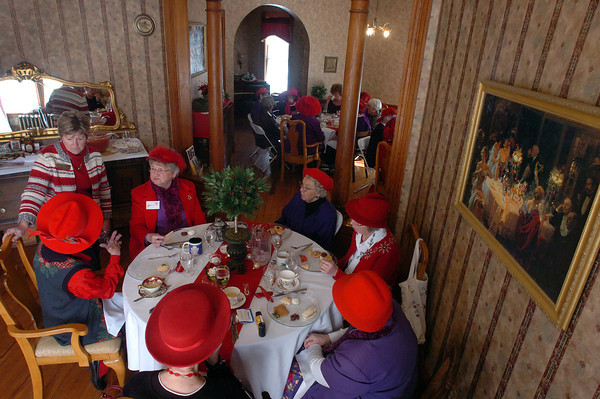 McCreery House owner Linda Stotz, left, talks with members of the Happy Hatters club as they have lunch on Wednesday at the historic house. The group, which meets every month at a different location, brought toys for the Santa Cops toy drive.