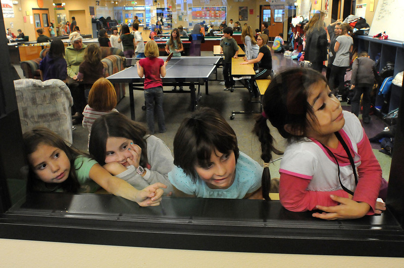 From right, Bianca Sandoval, 7, Venessa Bacon, 8, Brittany Ross, 9, and Tiger Lily Lopez, 8, try to get a better view of judging of the 4th annual Holiday Card Contest on Wednesday at the Boys and Girls Club in Loveland. The contest sponsored by McWhinney was open to all Larimer Boys and Girls members. McWhinney received a record 135 entries this year and donated $1,100 to the Larimer County Boys and Girls Club.