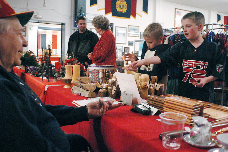 Tom Eckrich, left, spins a wooden top on his finger while chatting with Espn Sauer, 9, right, and Clay Walker, 9, at his table Saturday afternoon during a Christmas Bazaar at the Associated Veterans Club in downtown Loveland. At rear from left are Thomas Walker and Marilyn Walker.