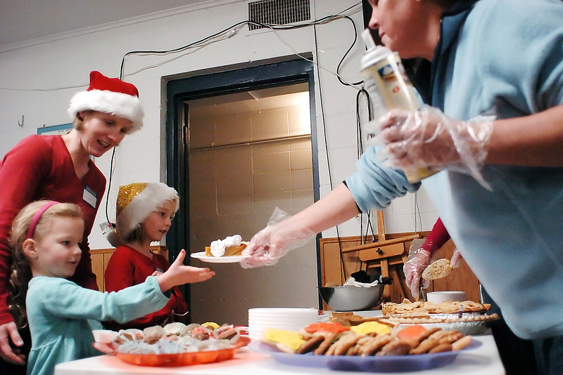 Volunteer Stephanie Effinger, right, hands a piece of pumpkin pie to 5-year-old Christine Doman who was getting desert with her mother, Juliann, and sister, Josie, 7, after having Christmas dinner at the Loveland Associated Veterans Club.