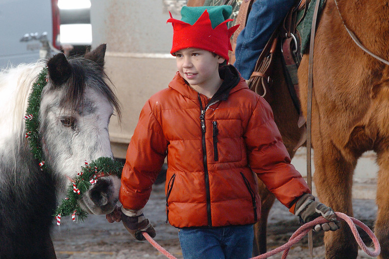 Eight-year-old Hunter Horsley dons a festive elf hat as he leads a horse named Sally around the parking lot at Safeway, 860 N. Cleveland Ave. where members of the No Tenderfoots Trail Riders prepared to ride on horseback through downtown Loveland singing Christmas carols on Saturday, Dec. 12, 2009.