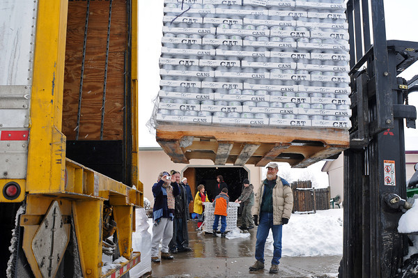 Volunteer Fred Renner, right, watches as a pallet of cat food is unloaded from a truck on Wednesday afternoon outside Duncan's Place, a cat rescue in Loveland. Cathy Campbell, founder of Duncan's Place, asked the Merrick Petfood Company for a donation of a couple of cases but the company sent her a donation of 14,000 pounds of catfood. She called up local rescues and asked volunteers to help distribute the food to them.