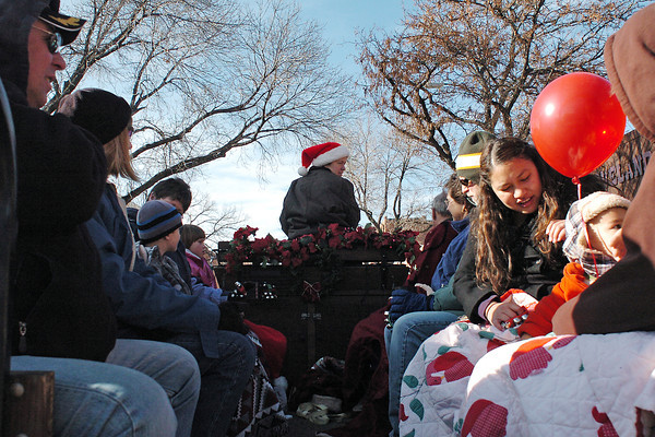 Michele Van Hare, back, drives a  horse-drawn wagon on Saturday filled with visitors to downtown  Loveland during the Winter Walk event.