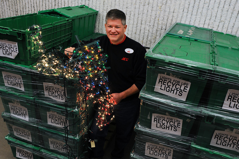 Holiday lights destined for recycling surround Clark Evans, manager or the Orchards Ace Hardware. The lights, donated by Lovelanders, are collected for recycling by Lights for Life, a company that turns over the proceeds to children with cancer.