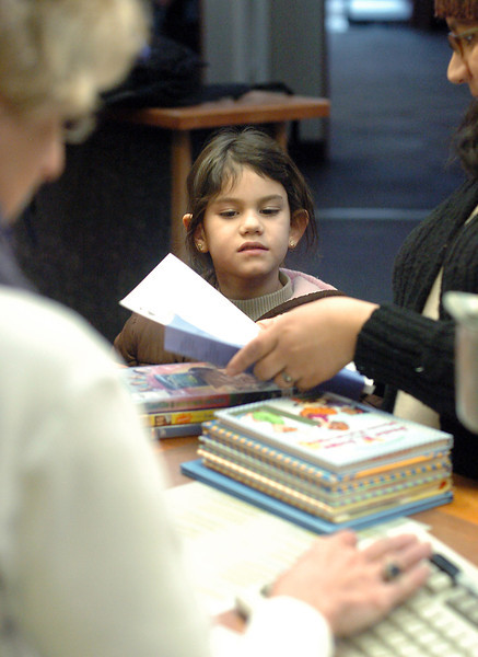 Eight-year-old Katelyn Kness is assisted by Joan Stephenson, left, as Katelyn and her mother, Elizabeth, check out some books at the Loveland Public Library on Wednesday.