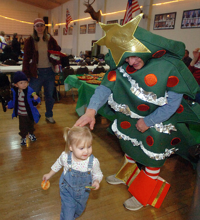 Dressed as a Christmas tree, Loveland Elks Club member Jim Sisler greets Cora Cox of Loveland, 2, as she darts past him during the Elks Christmas Party in downtown Loveland. Her cousin Jacob Simpson, 2, eats a cookie in the background after both children visited with Santa Claus.