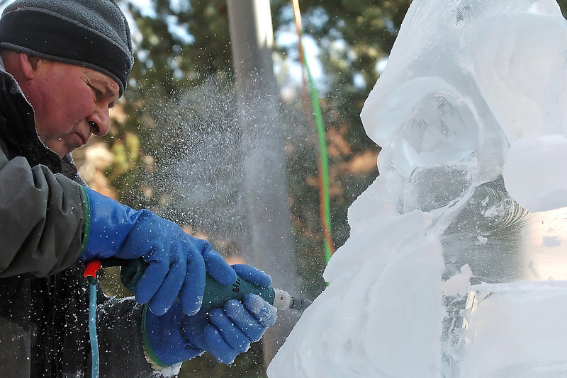 Shavings of ice fly as Michael Pizzuto works on an ice sculpture depicting Santa Claus on Saturday in Thompson Park during Winter Walk in downtown Loveland.
