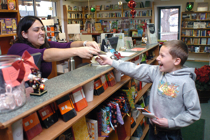 Eight-year-old Tyler Randol-Inskeep collects his change from Anthology Bookstore manager Teresa Martinez after purchasing a book and bookmarker Wednesday at the downtown Loveland store.
