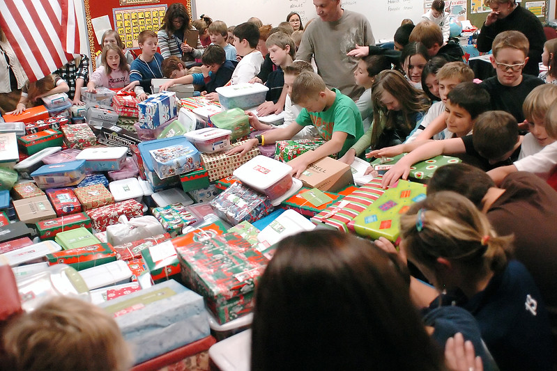 Fifth graders at Resurrection Christian School gather around a large pile of gift boxes and give thanks Thursday after collecting more than 2,200 boxes as gifts for poor children through Operation Christmas Child. The fifth-grade leadership team set a goal of collecting 2,017 boxes since they will graduate in 2017 and beat last year's record of 1,007 boxes of gifts.