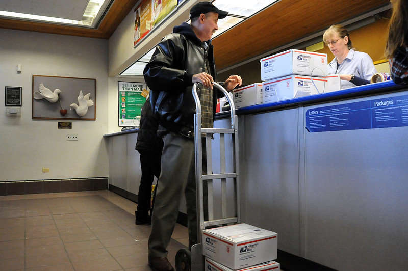 United States Postal Service employee Joanne Rocheleau, right, helps Mike Pappas of Loveland ship seven boxes destined for a Colorado National Guard unit in Ramadi, Iraq where his son, Sgt. Neil Pappas, is serving his third tour. Mike Pappas, who works at Thompson Medical Group, started getting donations of snacks, soups homemade cookies and hygiene products from coworkers to ship after he mentioned he was sending a care package to his son. Pappas has already sent eight other boxes to the unit.