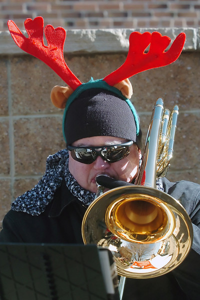 Todd Brubaker dons reindeer antlers as he plays his trombone with the group Santa's Trombones on Saturday in Thompson  Park while entertaining visitors to downtown Loveland.
